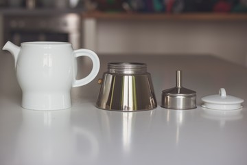 Disassembled steam white ceramic with metal coffee maker on a white table