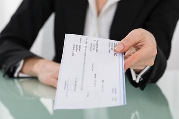 Businesswoman Hand Giving Cheque - fototapety na wymiar