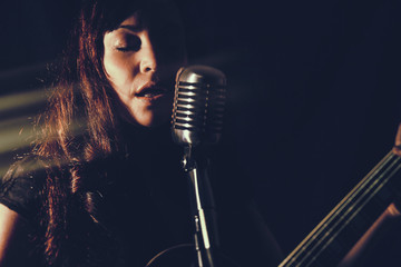 Pretty Woman Singing with Guitar. Attractive female playing an electric guitar and singing into a vintage microphone. Set in dark room with spot lighting and edited with vintage effects. Fotobehang