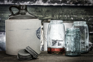 Vintage crock jug with mason jars, one with bourbon or whiskey within