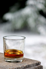 Bourbon Whiskey in a glass with snowy winter background