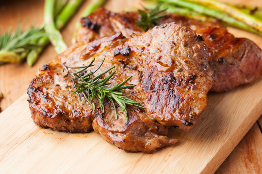 grilled pork chop with rosemary on wooden board