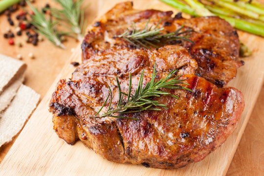 pork chop with rosemary on wooden board