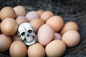 Hen eggs with human skull on wood background.