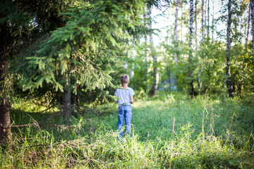 Young guy  standing in a forest on the grass