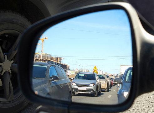Отражение автомобильной пробки во внешнем зеркале заднего вида автомобиля