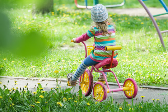 Back view full length portrait of preschooler girl riding kids pink and yellow tricycle on playground track