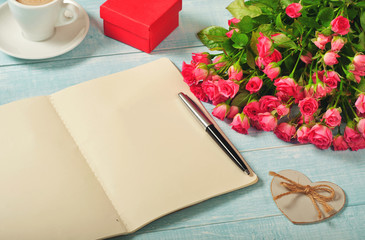 open notebook with blank pages with bouquet of roses