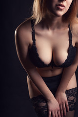 Sexy woman with big breasts on black background