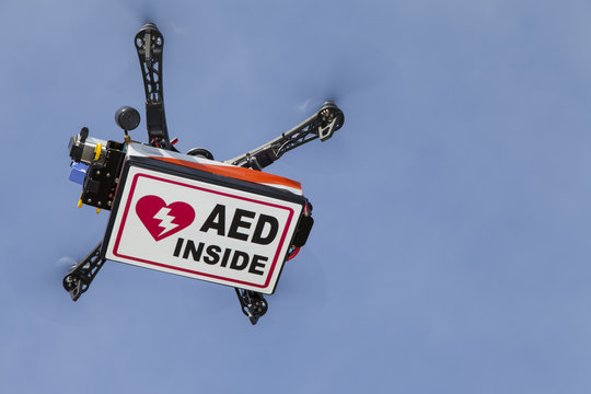 UAV drone quadrocopter with modern GPS navigation transporting Automated external defibrillator AED, against blue sky, space for text