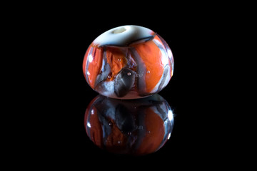 Transparent white and orange glass bead