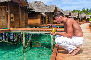 A man enjoying a coconut cocktail