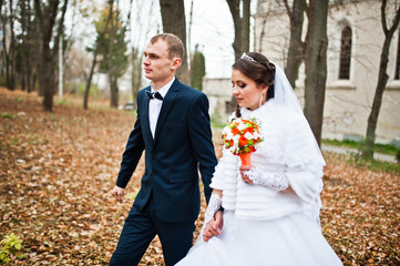 Happy wedding couple at autumn forest with fell leaves from the