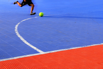 man kicking football on ground futsal. futsal plastic court floo