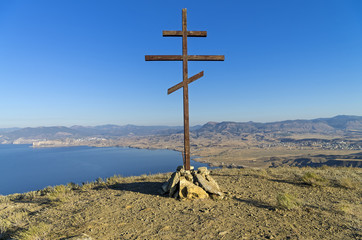 Orthodox cross on top of a mountain overlooking the sea. Crimea.