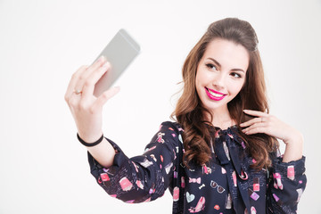 Cheerful charming young woman making selfie using smartphone