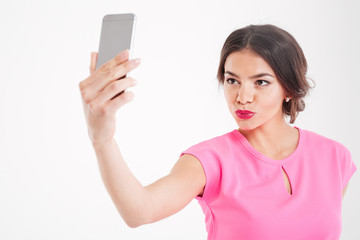 Cute woman making duck face and taking selfie using smartphone