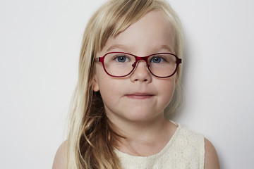 Cute little girl in glasses looking at camera