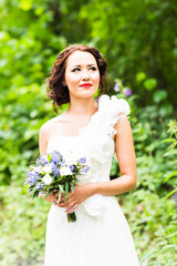 Bride holding bouquet of white calla lilies and blue flowers