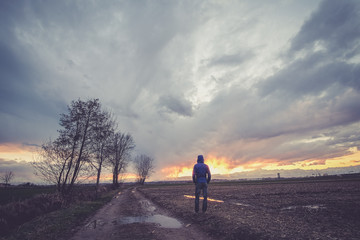 Man under a cloudy sky in the country watching the sunset