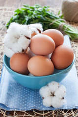 Eggs in blue bowl and cotton flowers