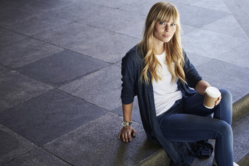 Wall Mural - Gorgeous blond woman sitting on steps, portrait