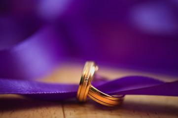 wedding rings and purple ribbon
