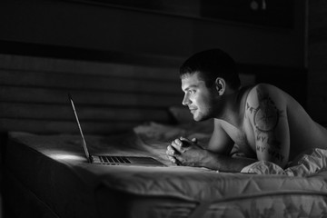 young man with naked torso on the bed with laptop/ black and white photo