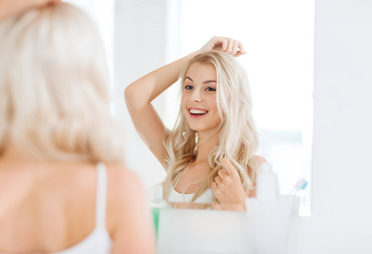 happy young woman looking to mirror at bathroom
