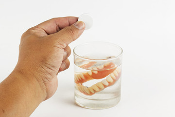 Hand holding cleaning tablets to a glass of False Teet