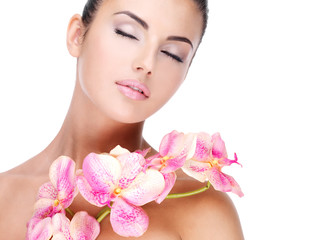 Wall Mural - Beautiful face of  woman with healthy skin and pink flowers