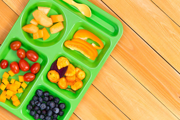 Child size lunch tray with fruit on wooden table