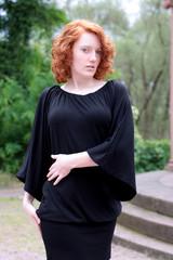 Frau mit roten Haaren im schwarzen Kleid