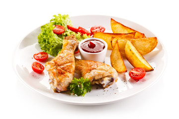 Grilled chicken legs with baked potatoes and vegetables