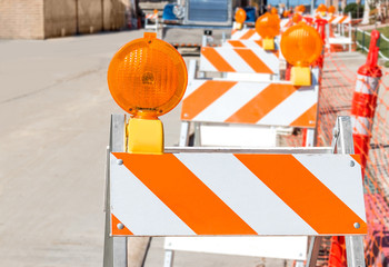 Row of bright orange and white striped construction warning barricades