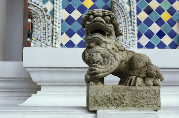 Stone statue of buddhist guardian lion dog used as decorative and symbolic element at the entrance to a structure on The Grand Palace territory, Bangkok