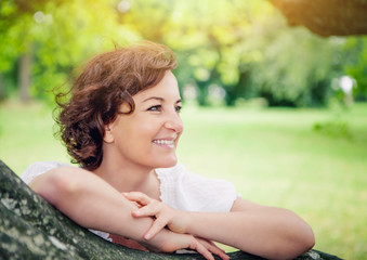 smiling woman leaning on a big branch