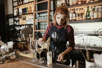 Barista woman making an alcohol cocktail at the bar