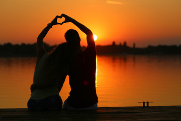 young couple doing heart shape with their hands on lake shore