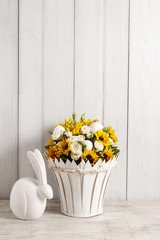 Bouquet of white roses and sunflowers and ceramic rabbit