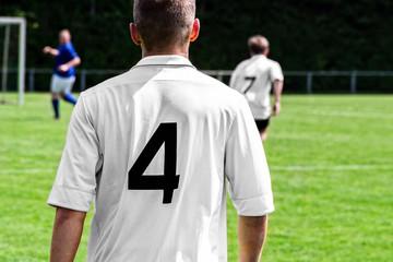 Fußballspieler auf dem Spielfeld im weißen Trikot von hinten