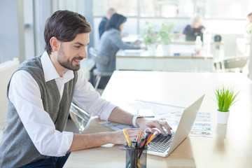 Attractive male designer is working with laptop