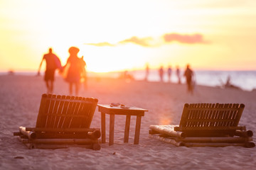 People leaving beach at sunset, two chaise longues in foreground