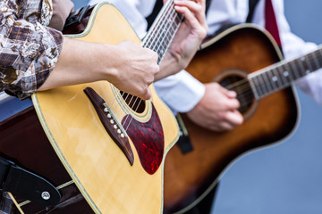 musicians playing on acoustic guitar