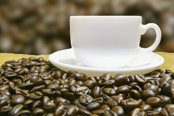 coffee in white cup on coffee bean table and blur background