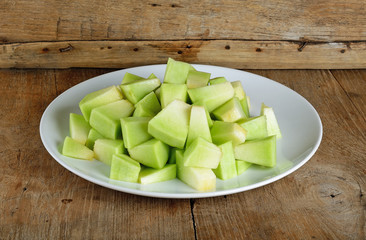 Sliced melon with plate on wooden background