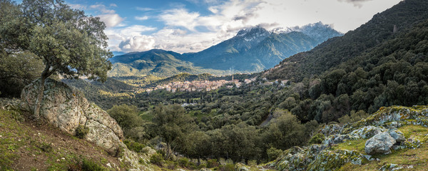 Village of Moltifao in Corsica with snow covered mountains behin