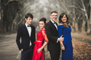 Bridesmaids and groomsmen of wedding couple posing in park