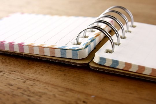 Colorful small spiral notebook on a wooden table