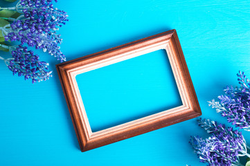Wooden photo frame and lavender twig on a blue background